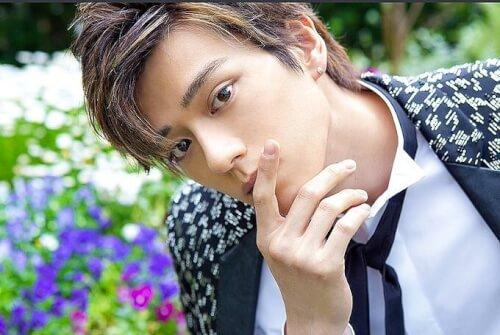 新田真剣佑が花の前でポージングしている写真画像