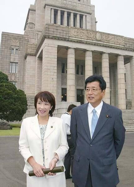 国会議事堂の前で高市早苗と山本拓が並んで立っている画像