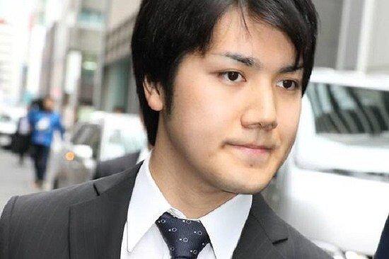 小室圭さんがスーツを着て待ちを歩いている画像
