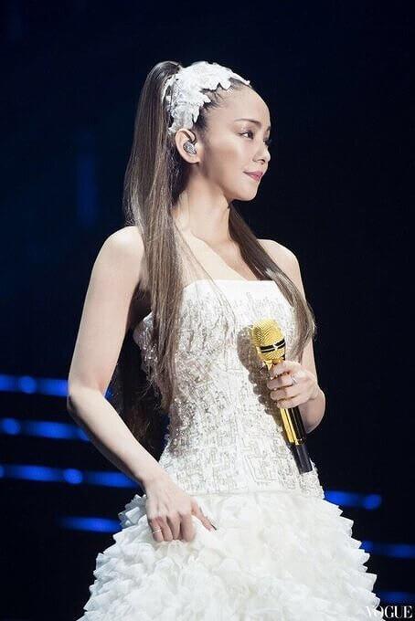 安室奈美恵が白いドレスに身を包み、マイクを持っている画像