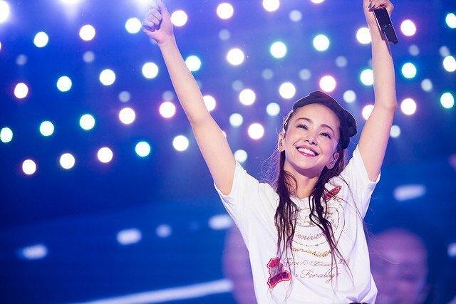 安室奈美恵がライブ中、観客に向けて手を振っている画像