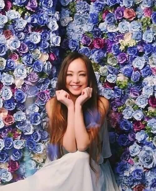 安室奈美恵さんが青い花に囲まれて笑っている画像