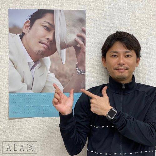 今井翼さんが自身のポスターの横で写真を撮っている画像