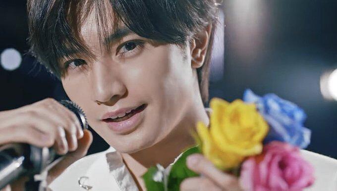 中島健人がカメラ目線で花を持って笑っている画像
