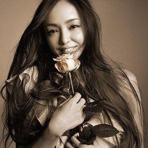 安室奈美恵さんが白い花を持って笑っている画像