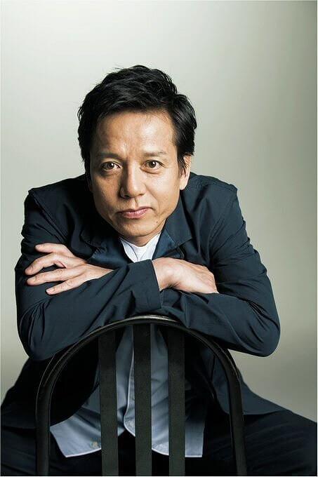 勝村政信さんが椅子に座ってポーズをしている画像